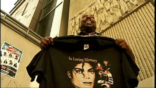vidéos et rushes de street seller with trolley full of michael jackson tishirts walks along hollywood boulevard 'walk of fame' candles and other memorabilia left on... - vendre