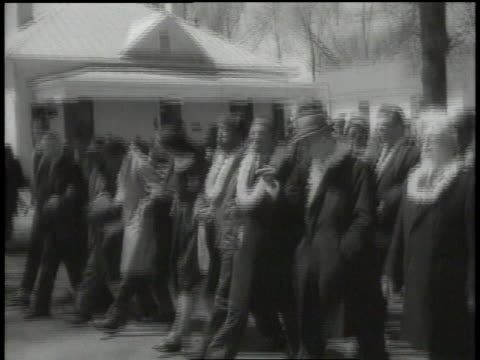 stockvideo's en b-roll-footage met street sign at corner / people marching peacefully, wearing leis / marchers crossing bridge on walkways with jeep driving on road - 1965