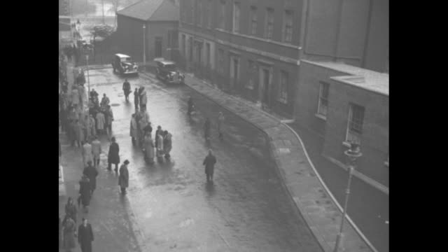 downing st / high angle view of a wet street in front of the prime minister stanley baldwin's london home / pan of crowd to door of number 10 / vs... - downing street video stock e b–roll