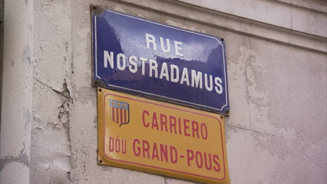 A street sign for Rue Nostradamus hangs on an exterior stone wall at Saint Remy de Provence in France.