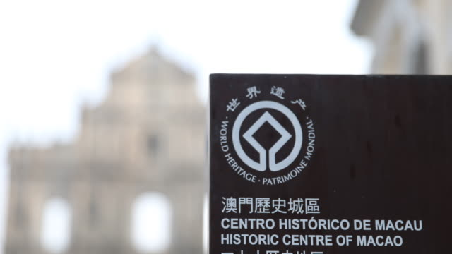 Street sign in two languages informs about the historical centre of Macau with the ruins of St Paul's in the background