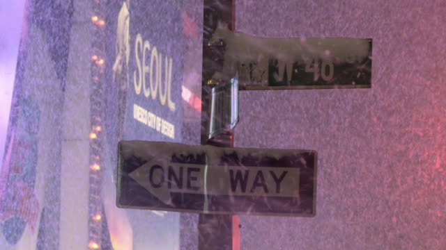 stockvideo's en b-roll-footage met a street sign is covered with snow during a snow storm. - straatnaambord