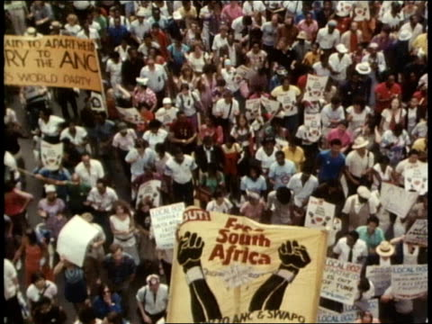 vídeos de stock, filmes e b-roll de street sign on 42nd street inscribed nelson and winnie mandela corner / crowds of enthusiastic demonstrators carrying a wide variety of banners flags... - nelson mandela