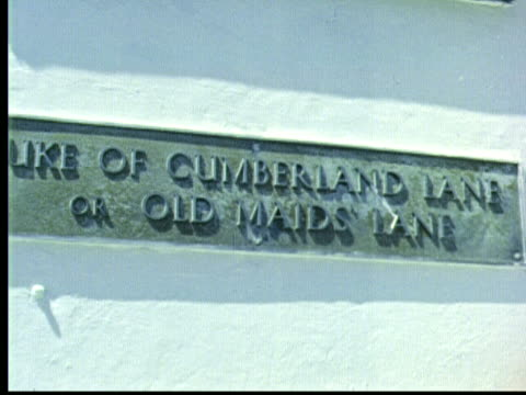 """street sign on stone wall: due of cumberland lane or old maid's lane. jonathan winters walks towards camera shaking like old man / hamilton, bermuda - """"archive farms"""" stock videos & royalty-free footage"""