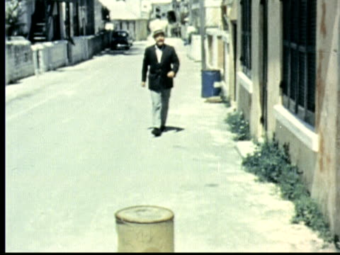 "street sign on wall: shinbone alley. jonathan winters walks towards camera and bumps shin into barrel. winces in pain / hamilton, bermuda - ""archive farms"" stock videos & royalty-free footage"