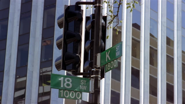 street signs at corner of k street and 18 street with us flag reflected in window of office building / washington, dc - lobby stock videos & royalty-free footage