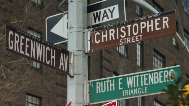street signs at the corner of christopher street and greenwich ave.  the ruth e wittenberg triangle and a one way sign. - one way stock videos & royalty-free footage