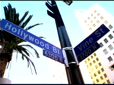 street signs for hollywood boulevard and vine street in california - 道路名の標識点の映像素材/bロール