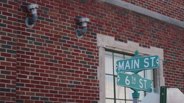 "street signs in a small americana town read; ""6th and main street."" - small town stock videos & royalty-free footage"