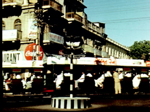1960 montage street signs: shah ah iraq and elphinstone st. karachi street corner, trolleys cross. large white building with pan american airways office on street level / karachi, pakistan - sindh pakistan stock videos and b-roll footage