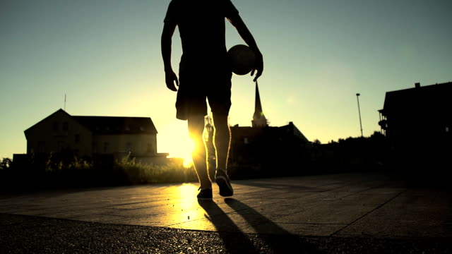 hd super slow-mo: street soccer player walking away - football stock videos & royalty-free footage
