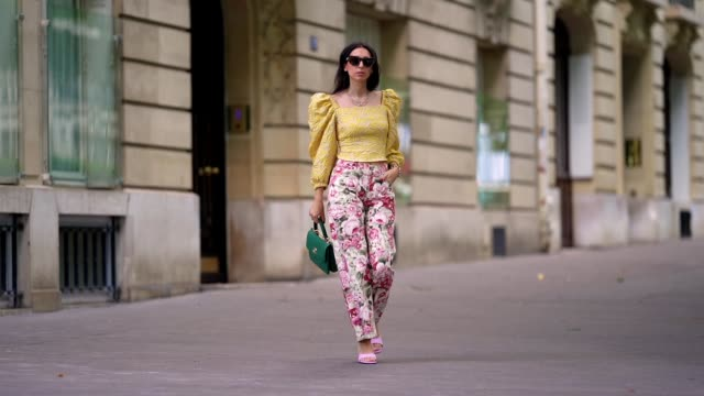 street style photo session with gabriella berdugo wearing kenzo sunglasses, a yellow ruffled top with puff sleeves and shoulder pads from avavav,... - street style点の映像素材/bロール