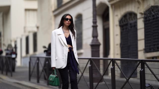 street style photo session with gabriella berdugo wearing prada sunglasses, shaker jewel jewelry, a white oversized blazer jacket from salisa, a... - street style点の映像素材/bロール