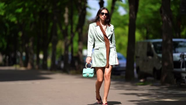 street style photo session with gabriella berdugo wearing prada sunglasses, a rolex watch, colorful shaker jewel bracelets, a turquoise quilted... - street style点の映像素材/bロール