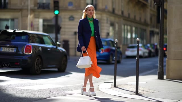 street style photo session with leonie hanne wearing golden earrings, a golden necklace, a dark navy blue prada blazer jacket, a green ruffled silky... - navy blue stock videos & royalty-free footage
