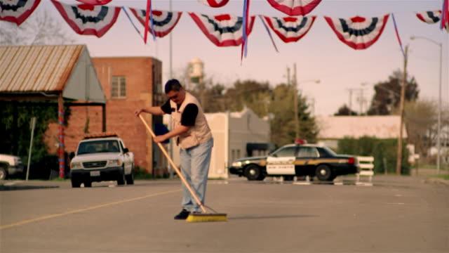 Street sweeper cleaning street / American flag banner strung across street / California