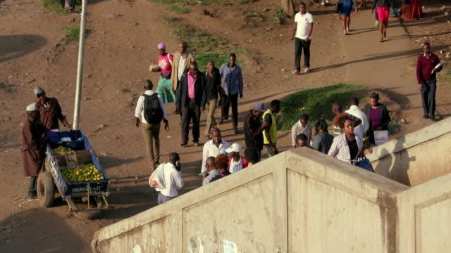 street trader sells fruit & pedestrians climb footbridge nairobi  kenya  africa - footbridge stock videos & royalty-free footage
