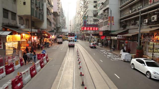 vídeos de stock, filmes e b-roll de ws pov street traffic as seen from moving tram / hong kong, china - ponto de vista de bonde