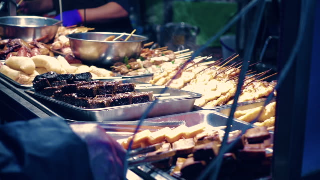 A street vendor cooks skewers of meat on a barbecue