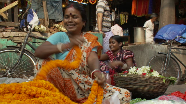 a street vendor in a sari packages flower garlands in calcutta. - kolkata stock videos & royalty-free footage