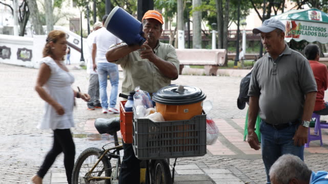 street vendor is pouring a drink from a big thermos jug into small cups. - jug stock videos & royalty-free footage