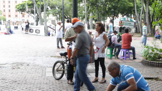 a street vendor on a bicycle it talking to a female costumer while a man is trying to feed pigeons in front of them - south america stock videos & royalty-free footage