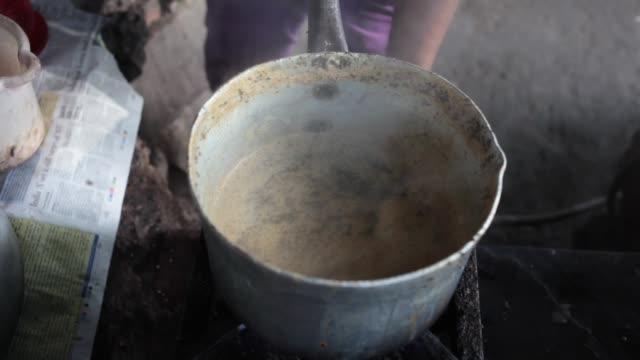 a street vendor peels potatoes while preparing breakfast in new delhi india on monday sept 9 a street tea stall worker prepares morning chai tea at a... - straßenverkäufer stock-videos und b-roll-filmmaterial