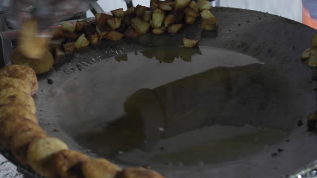 a street vendor prepares aloo tikki, an indian subcontinent snack made of boiled potatoes, onions and various spices in a n open tawa or tava, a large frying pan - croquette stock videos and b-roll footage
