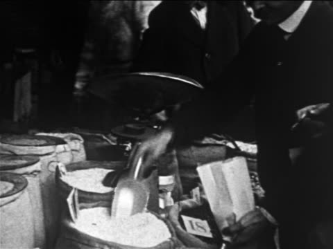b/w 1913 street vendor scooping dry goods from sack into paper bag + weighing it / lower east side - 1913 stock videos & royalty-free footage