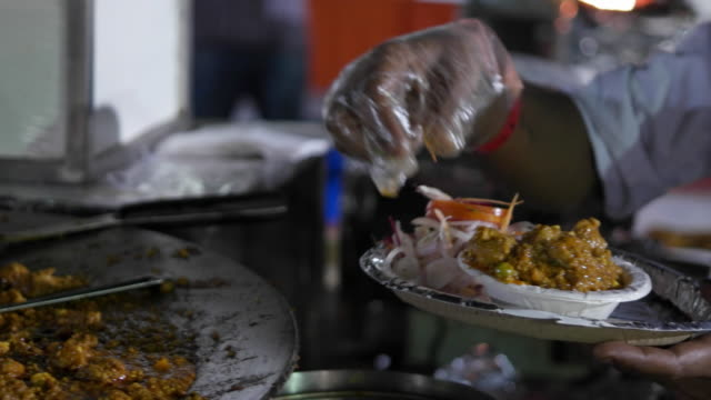 a street vendor serving a small meal with vegetable masala dish served along with rumali / roomali roti, onion salad, green chutney, topped with chaat masala served hygienically on a disposable plate with paper napkin - お玉点の映像素材/bロール