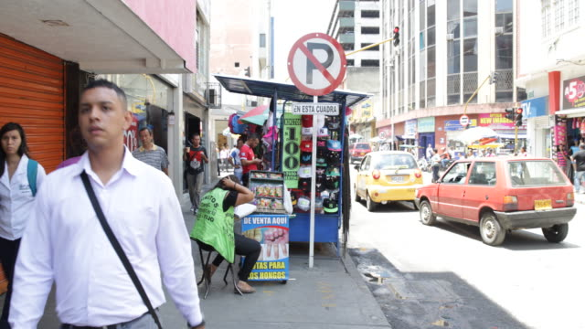 A street vendor sitting on a little stool on the sidewalk