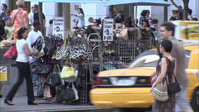 vídeos de stock e filmes b-roll de ms, street vendor stand full of handbags, fifth avenue, new york city, new york, usa - feirante