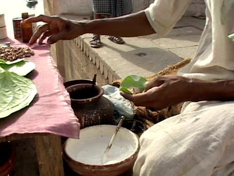 vídeos de stock, filmes e b-roll de cu, street vendor's hands preparing benarasi paan (betel leaf), varanasi, uttar pradesh, india - lanche