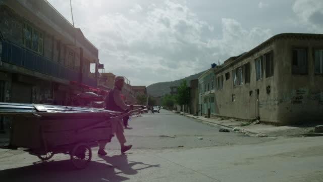 street vendors walking down a deserted kabul street - kabul stock-videos und b-roll-filmmaterial