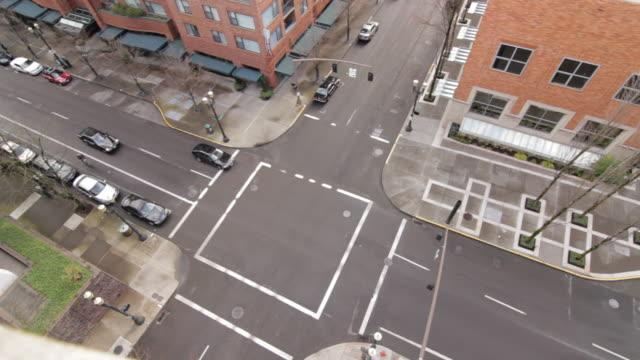street view from a rooftop showing cars and cyclists passing through an intersection - ecke eines objekts stock-videos und b-roll-filmmaterial
