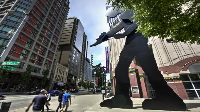 W/S street view time lapse of the 'Hammering Man' kinetic sculpture outside Seattle Art Museum with foot and car traffic in the background