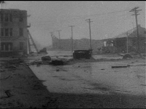 street w/ some wind, concrete foundation w/ no building fg, flooded street. newspaper headline: '...killed in florida, 150 missing, pensacola... - 1926年点の映像素材/bロール