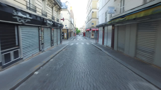 street with closed restaurants and souvenir shops a man runs and two pedestrians may 6 2020 in paris france - three people stock videos & royalty-free footage