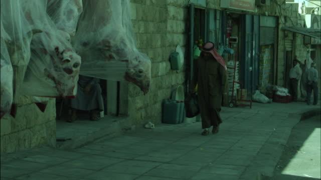 vídeos de stock e filmes b-roll de street with dead sheep hanging outside butcher's shop, jordan - ilhas do canal da mancha