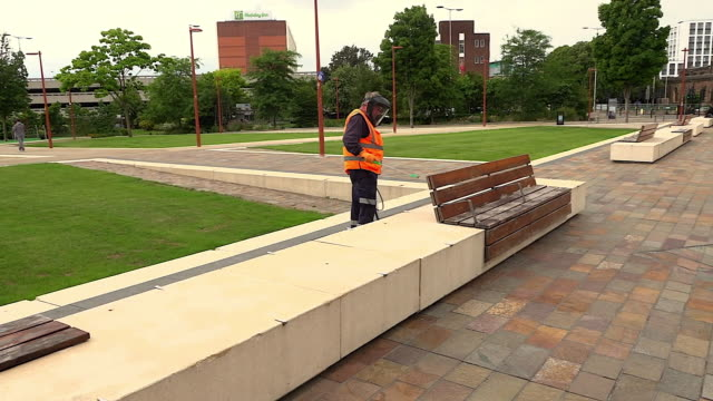 a street worker with a protective mask sanitising a public bench to prevent coronavirus transmission - decor stock videos & royalty-free footage