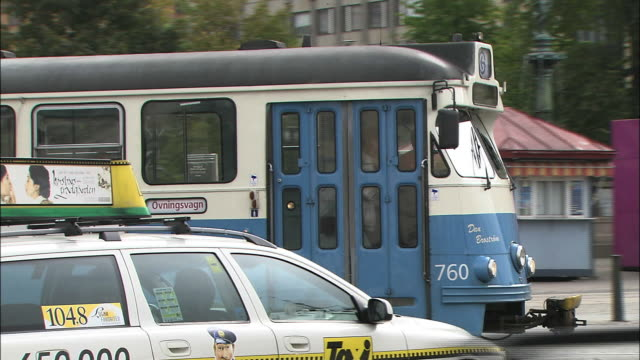 stockvideo's en b-roll-footage met a streetcar and other traffic pass through gothenburg, sweden. - tram