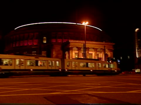 stockvideo's en b-roll-footage met a streetcar and pedestrians cross the intersection at st peters square and the central library in manchester england - sint pietersplein