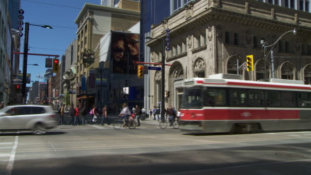 A streetcar and traffic passes by a bank and crosses the intersection of Queen ST and Yonge ST.  The crosswalks are filled with people crossing the St..