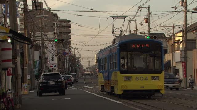 streetcar and tsutenkaku, osaka, japan - 老朽化点の映像素材/bロール