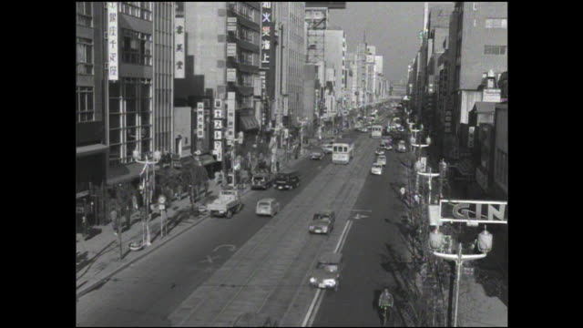 a streetcar maneuvers down a street on the last day of operation for the toden ginza line. - 1960~1969年点の映像素材/bロール