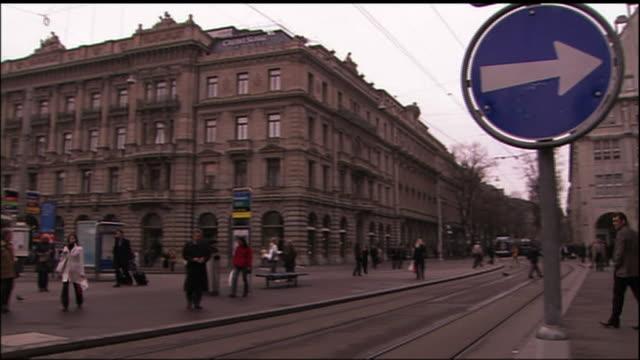 A streetcar passes pedestrians in Zurich.