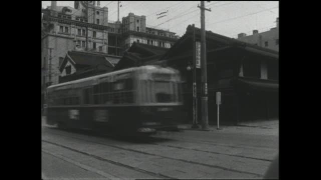 A streetcar transports commuters on an Osaka city street.