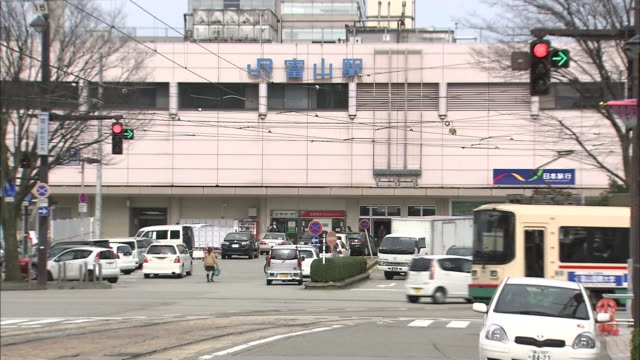 a streetcar turns a corner in front of  the jr toyama station in japan. - toyama prefecture stock videos and b-roll footage