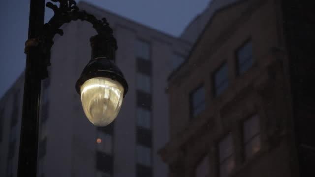 vidéos et rushes de streetlight lights up during snowstorm - montréal