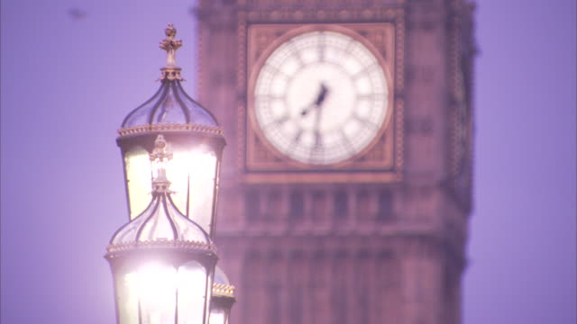 Streetlights shine in front of the Big Ben clock tower in London, England.